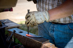 Expert Blacksmith forms steel into a form Royalty Free Stock Photography