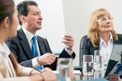 Expert businessman sharing his view during a decision-making mee. Side view of an expert businessman sharing his view about the development of an important Royalty Free Stock Photography