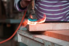 Expert carpenter burning a wood slab with a professional gas burner. Flames and smoke, fire and timber. Detailed shot of a professional carpenter, in his stock images