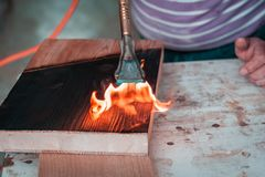 Expert carpenter burning a wood slab with a professional gas burner. Flames and smoke, fire and timber. Detailed shot of a professional carpenter, in his stock photo