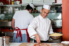 Expert chefs at work inside restaurant kitchen Stock Images