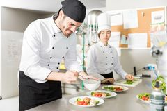 Expert Cook Adding Flavor To Dish In Kitchen. Young male chef pouring sauce on tasty meat at kitchen counter royalty free stock photo