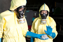 Expert disposing biohazard. Biohazard expert in yellow protection sweet disposing infested material stock image