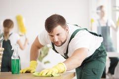 Expert en matière de nettoyage lavant la table photo stock