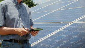 Expert Energy Engineer Inspects Solar Power Panel