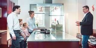 Expert explaining new kitchen to family looking for one stock photography