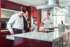 Expert explaining new kitchen to family looking for one. Pointing at some interesting features of the current model royalty free stock photo