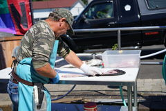 Expert filleting a fish. Sport fishing is big business all around the world. Most fisherman pay workers at the docks to clean and fillet their fish before taking Royalty Free Stock Images