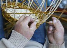 Expert hands of craftsman creates a woven wicker basket Stock Photo