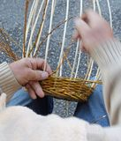 Expert hands of the elderly craftsman creates a woven wicker bas Stock Photo