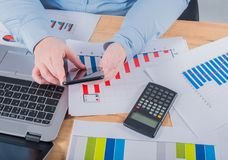 Expert in her business. Woman making some notes in notebook and looking at graphs at her workplace.  stock photography
