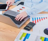 Expert in her business. Woman making some notes in notebook and looking at graphs at her workplace.  stock images