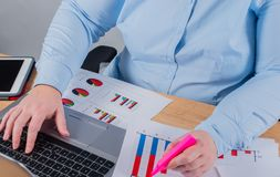 Expert in her business. Woman making some notes in notebook and looking at graphs at her workplace.  royalty free stock images