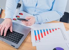 Expert in her business. Woman making some notes in notebook and looking at graphs at her workplace.  stock photo
