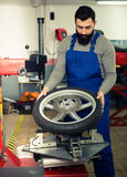 Expert inspects a wheel for a motorcycle Stock Photos