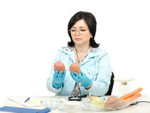 Expert looking at two red potatoes in laboratory Stock Photo