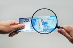 Expert with magnifying glass checks suspicious money. Search watermarks on paper of the fake bills. magnifying glass, magnifier, magnifying lens, magnifying royalty free stock photo