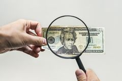 Expert with magnifying glass checks suspicious money. search watermarks on paper of the fake bills. magnifying glass, magnifier, m. Agnifying lens, magnifying royalty free stock images