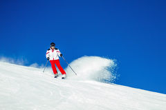 Expert Male Skier Carving Through Fresh Snow. Seasoned male skier carving down a snowcovered ski slope Royalty Free Stock Photography