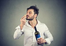 Expert man smelling wine cork. Bearded man in white shirt enjoying perfect smell of wine bottle cork being expert in wine grades royalty free stock image