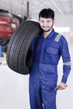 Expert mechanic carrying a tire in workshop. Portrait of a young professional mechanic walking in the workshop while carrying a tire Stock Images