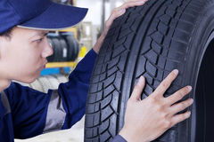 Expert mechanic checking a tyre Royalty Free Stock Images