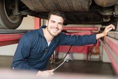Expert med skiftnyckeln som reparerar bilen i garage royaltyfria foton