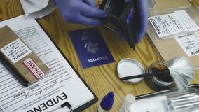 Expert police officer examining American passport of a evidence bag in laboratory of criminology. Conceptual image stock video