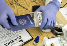 Expert police officer examining American passport of a evidence bag in laboratory of criminology. Conceptual image stock photos