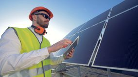An expert is regulating work of a solar array with his tablet computer. Green energy concept. An expert is regulating work of a solar array with his tablet stock video footage