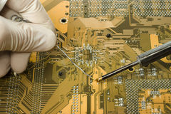 Expert is repairing motherboard. Close up view of expert in white mitten is repairing circuit board using soldering iron and solder Royalty Free Stock Photo