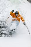 Expert skier skiing powder snow in Stowe, Vermont,. Expert skier skiing in deep powder snow in front of a frozen waterfall, Mt. Mansfield, Stowe, Vermont, USA Stock Photos