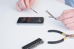 Expert technician is repairing a broken smart-phone. Table stock image