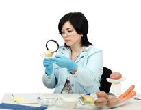 Expert viewing closely a onion in laboratory Stock Photos