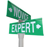 Expert Vs Novice Two Way Road Sign Skills Experience Expertise. Expert Vs Novice words on green two way road signs to illustrate the power of skills, expertise Stock Images