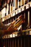 Expert in winemaking choose elite white wine in cellar. Males hand on background of shelves with wine, sommelier at work Stock Images