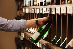 Expert in winemaking choose elite white wine in cellar. Males hand on background of shelves with wine, sommelier at work Royalty Free Stock Image