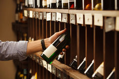 Expert in winemaking choose elite white wine in cellar. Males hand on background of shelves with wine, sommelier at work Royalty Free Stock Photo