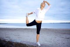 Expert yoga poserar på strand Arkivfoton
