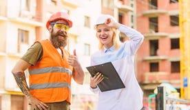 Experte und Erbauer stehen ?ber VersorgungsBaumaterialien in Verbindung Kauf von Baumaterialien Baugewerbe stockbilder