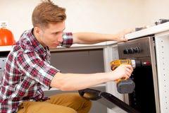 Expertengruppe, die den Küchenofen repariert Stockfoto