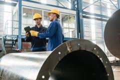 Experter som kontrollerar information på minnestavlaPC i en modern fabrik royaltyfri foto