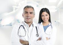 Expertise doctor beautiful nurse hospital. Expertise gray hair doctor beautiful nurse in hospital white corridor stock image