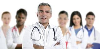 Expertise doctor multiracial nurse team row. Expertise gray hair doctor multiracial nurse team row over white stock photos