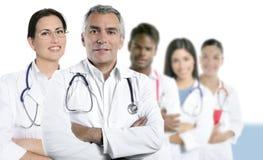 Expertise doctor multiracial nurse team row. Expertise gray hair doctor multiracial nurse team row over white stock photo