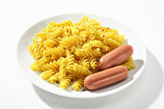 Expertly cooked fusilli with spice served with an accompanying sausages Stock Image