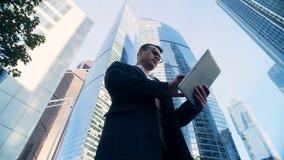 Experto financiero acertado masculino rodeado por los edificios urbanos, rascacielos Tiro épico rojo de la cámara del cine