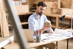Experto joven pensativo de la madera de construcción que piensa sobre bosquejos del producto en taller Imagenes de archivo