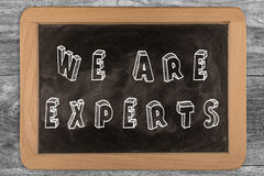 We are experts - chalkboard with outlined text. On wood Stock Image