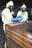 Experts disposing infested material. Warning because of hazard in factory stock photos